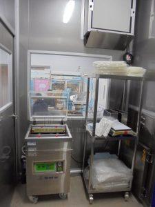 包裝室內的不鏽鋼包材架及真空包裝機